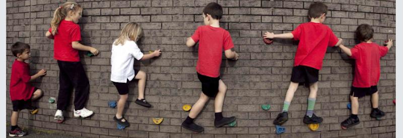 Children Climbing A Wall